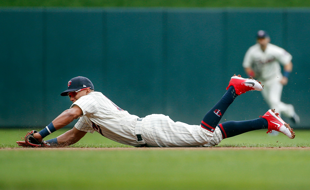 . Minnesota Twins second baseman Ehire Adrianza dives for a ground ball hit by Cleveland Indians designated hitter Edwin Encarnacion in the first inning of a baseball game Wednesday, Aug. 1, 2018, in Minneapolis. Encarnacion was out a first on the play (AP Photo/Bruce Kluckhohn)