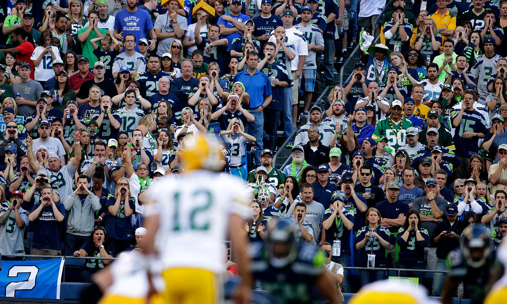 . Seattle Seahawks fans yell as Green Bay Packers quarterback Aaron Rodgers (12) tries to call a play in the first half of an NFL football game, Thursday, Sept. 4, 2014, in Seattle. (AP Photo/Scott Eklund)