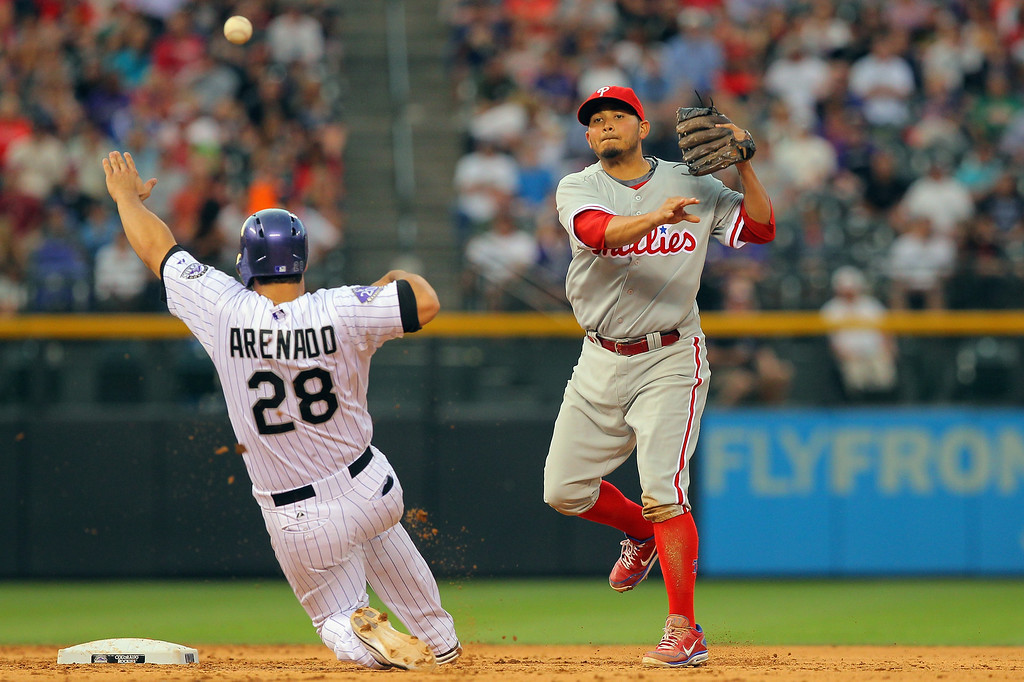 . DENVER, CO - JUNE 14:  Shortstop Freddy Galvis #13 of the Philadelphia Phillies turns a double play on Nolan Arenado #28 of the Colorado Rockies at Coors Field on June 14, 2013 in Denver, Colorado.  (Photo by Doug Pensinger/Getty Images)