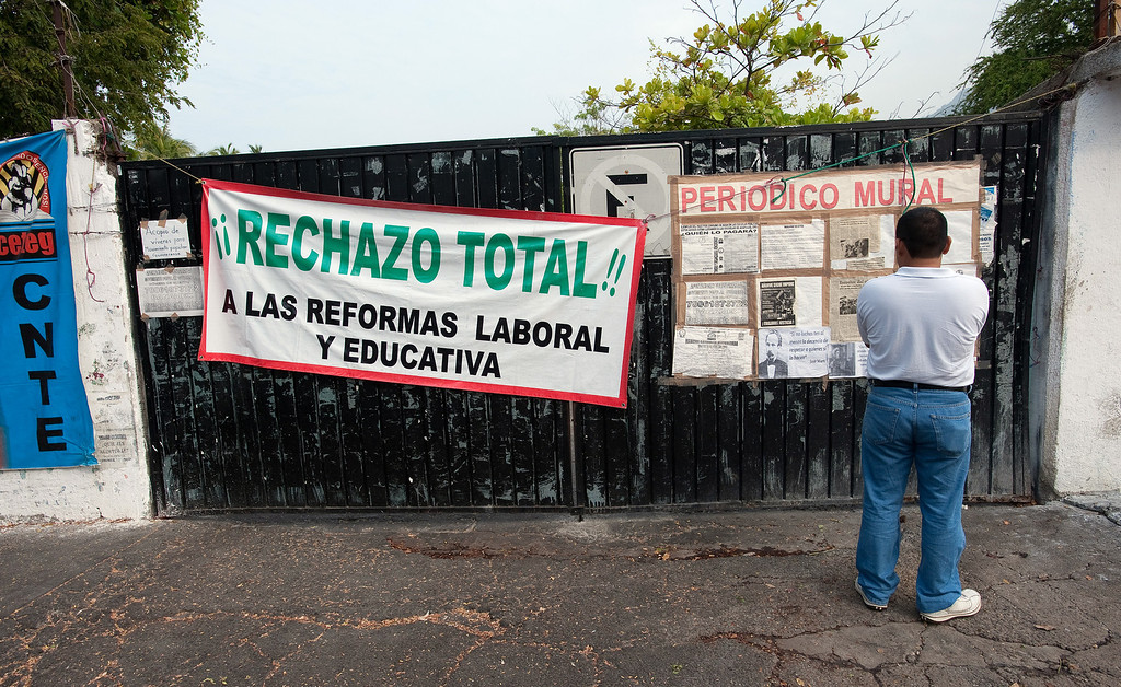""". Mexican journalists are under siege throughout the country both from organized crime and abusive government authorities. A man reads a \""""wall newspaper\"""" with information about the on-going teacher\'s strike in Acapulco. The large sign reads \""""Complete rejection of the education and labor reforms\"""" in reference to the proposed reforms being advanced by President Enrique Pena Nieto. (Keith Dannemiller/MCT)"""