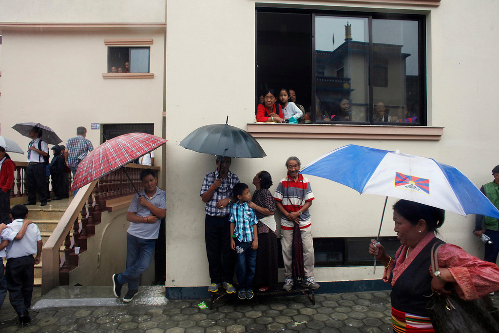 . Tibetans wait in the rain to participate in celebrations marking the birthday of their spiritual leader the Dalai Lama in Katmandu, Nepal, Saturday, July 6, 2013. The Tibetan leader turned 78 today. (AP Photo/Niranjan Shrestha)
