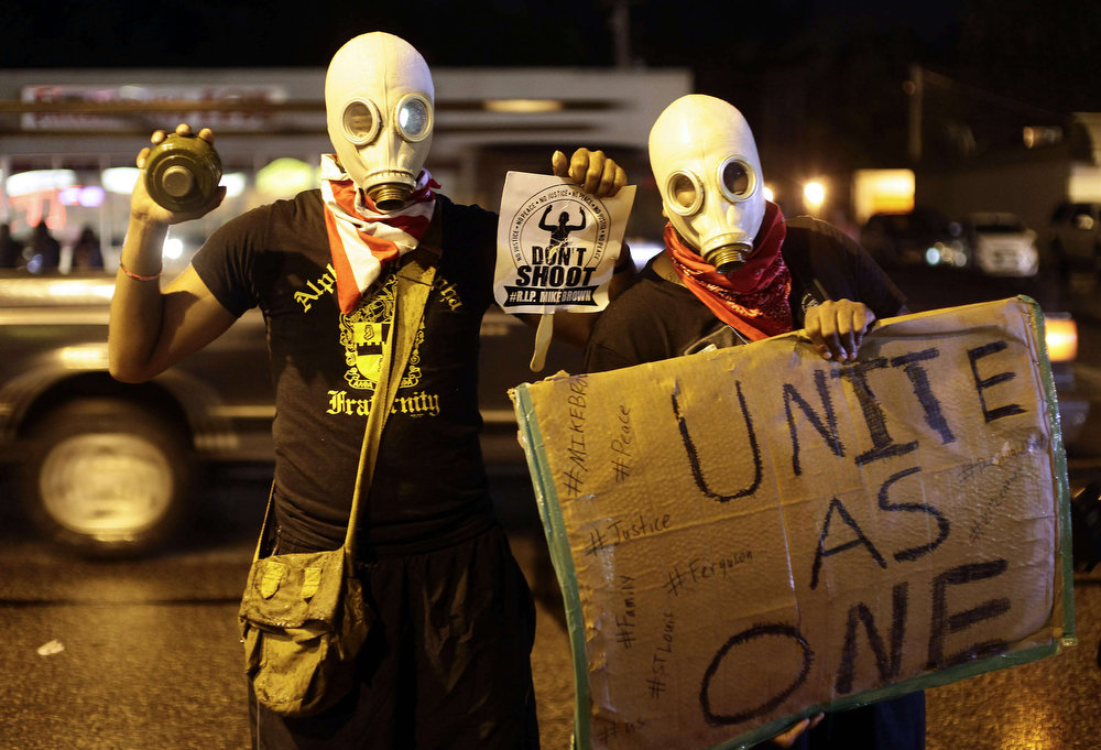 . Masked demonstrators protest against the August 9 police shooting of 18-year-old Michael Brown by holding up signs on the streets of Ferguson, Missouri late on August 16, 2014.  A crowd of some 200 demonstrators defied a curfew that came into effect in Ferguson early on August 17, days after police shot dead the unarmed black teen, triggering a wave of rioting.   Joshua LOTT/AFP/Getty Images
