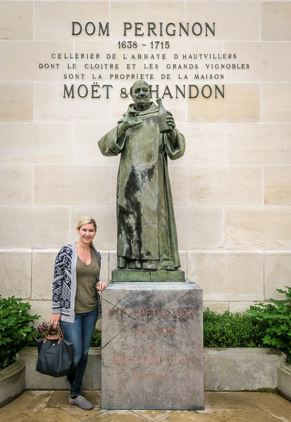 Woman standing next to statue of the monk, Dom Perignon in front of the Moet & Chandon winery in France.