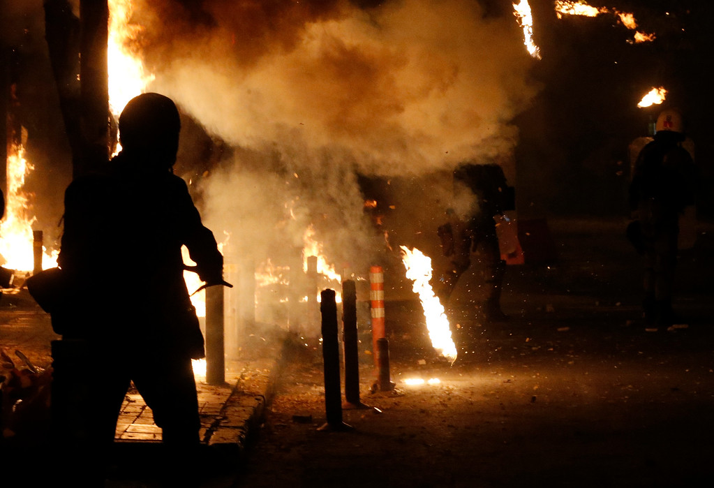 . Riot police try to avoid petrol bombs thrown by protesters during clashes in the Athens neighborhood of Exarchia, a haven for extreme leftists and anarchists, on Saturday, Dec. 6, 2014.   (AP Photo/Petros Giannakouris)