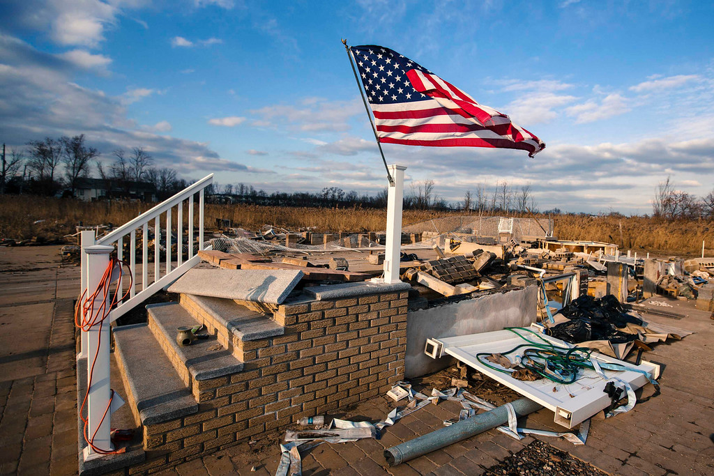 . A U.S. flag flies over the foundation of a home destroyed by the storm surge of superstorm Sandy in the Staten Island borough neighborhood of Oakwood in New York, November 28, 2012.  REUTERS/Lucas Jackson