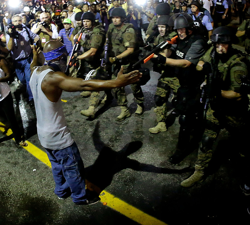 . Police arrest a man as they disperse a protest in Ferguson, Mo., early Wednesday, Aug. 20, 2014. On Saturday, Aug. 9, a white police officer fatally shot unarmed 18-year-old Michael Brown, who was black, in the St. Louis suburb. (AP Photo/Charlie Riedel, File)