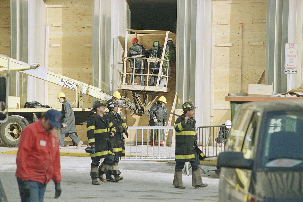 Description of . Firefighters walk past workers installing plywood over broken windows at the World Trade Center in New York on Feb. 27, 1993.  At least five people are dead and hundreds were injured as a result of an explosion at the World Trade Center.  (AP Photo/Richard Drew)