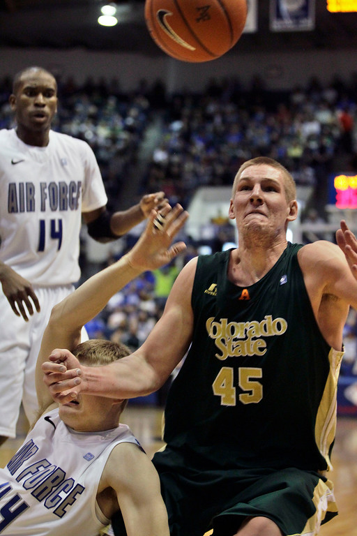 . Colorado State\'s Colton Iverson, right, struggles to get a loose ball as Air Force\'s Chase Kammerer, lower left, falls during the second half of an NCAA college basketball game in Air Force Academy, Colo., Saturday, Feb. 16, 2013. Colorado State won 89-86. (AP Photo/Brennan Linsley)