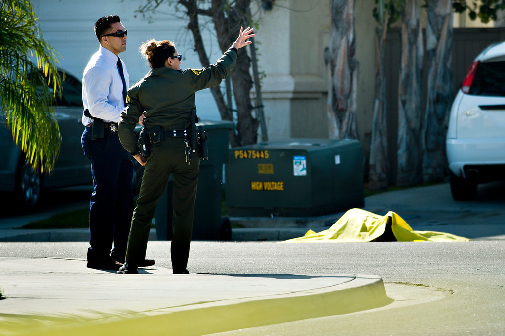 . The body of a man killed by the deputies lays covered as officials investigate the scene at the 5400 block of Brushwood Court in Chino Hills on Friday, March 28, 2014. (Photo by Watchara Phomicinda/ San Gabriel Valley Tribune)