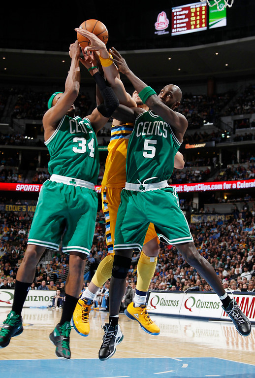 . Boston Celtics forwards Paul Pierce, left, and Kevin Garnett, right, box out Denver Nuggets forward JaVale McGee for a rebound during the fourth quarter of the Nuggets\' 97-90 victory in an NBA basketball game in Denver on Tuesday, Feb. 19, 2013. (AP Photo/David Zalubowski)