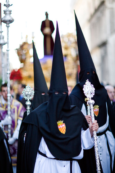 Hooded penitents carrying sticks with their brotherhood emblem in front of a float with the image of Christ.