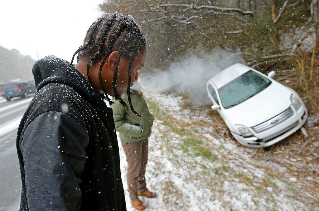 . Jesse Hatcher looks over his crashed car after he says another motorist caused him to lose control of his car and spin out off I-20 West near Conyers, Ga.,  on Tuesday, Jan. 28, 2014. Light snow moved into parts of north Georgia by midmorning and began coating the metro Atlanta region by noon.  (AP Photo/Atlanta Journal-Constitution, Curtis Compton)