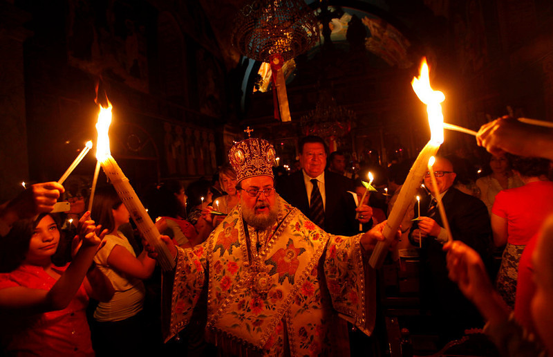 . A priest holds candles during the ceremony of the Holy Fire at a Greek Orthodox church in Gaza City, Sunday, May 5, 2013. Eastern Orthodox churches celebrate Easter, the resurrection of Jesus, on Sunday.   (AP Photo/Hatem Moussa)