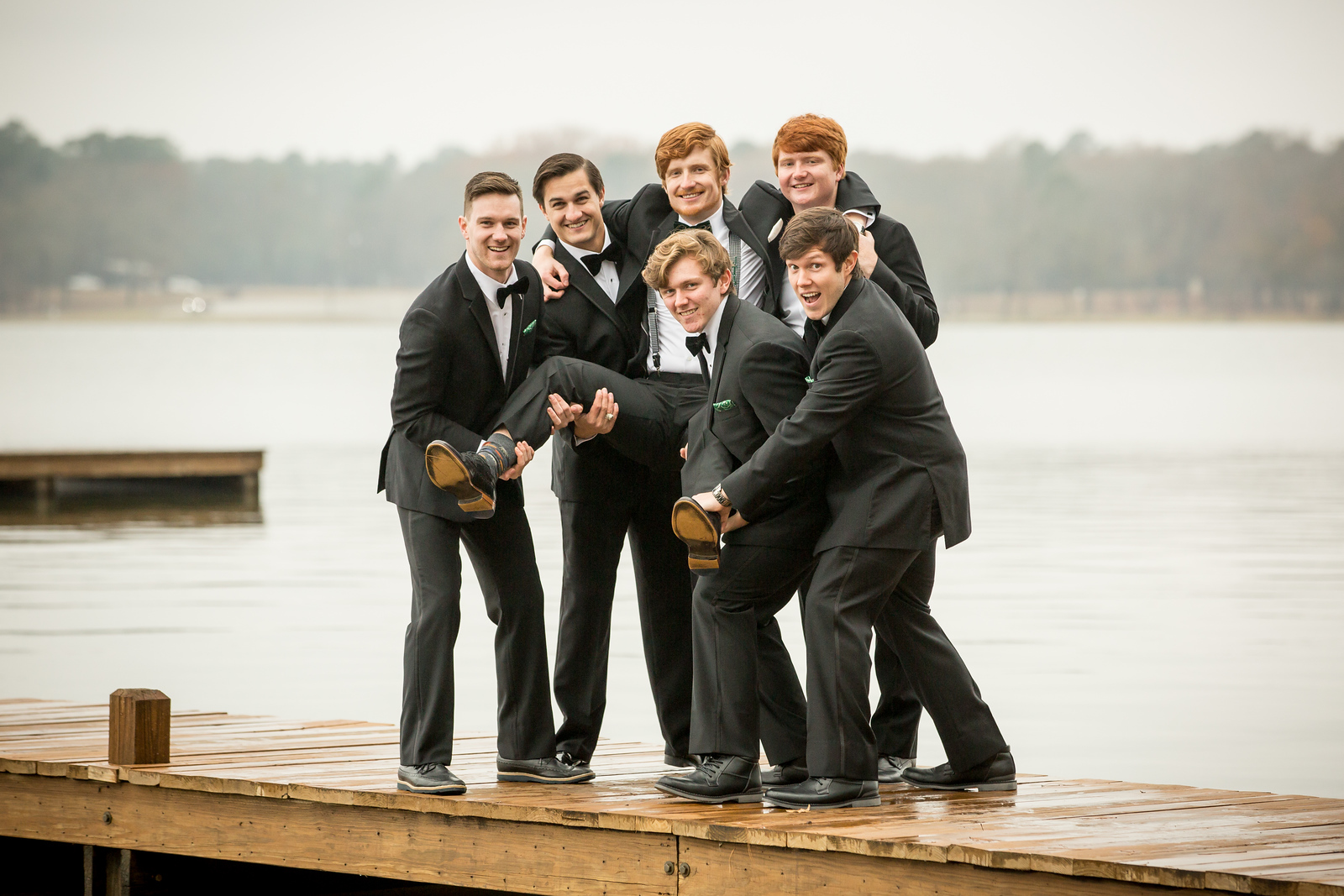A groom being held up in the air on a dock in Tyler Lake by his groomsmen.