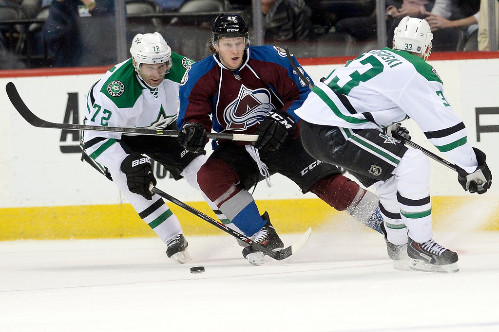 . DENVER, CO - DECEMBER 16: Colorado Avalanche center Nathan MacKinnon (29) controls the puck as Dallas Stars right wing Erik Cole (72) and defenseman Alex Goligoski (33) defend during the third period of the Avs\' 6-2 win. The Colorado Avalanche hosted the Dallas stars at the Pepsi Center. (Photo by AAron Ontiveroz/The Denver Post)