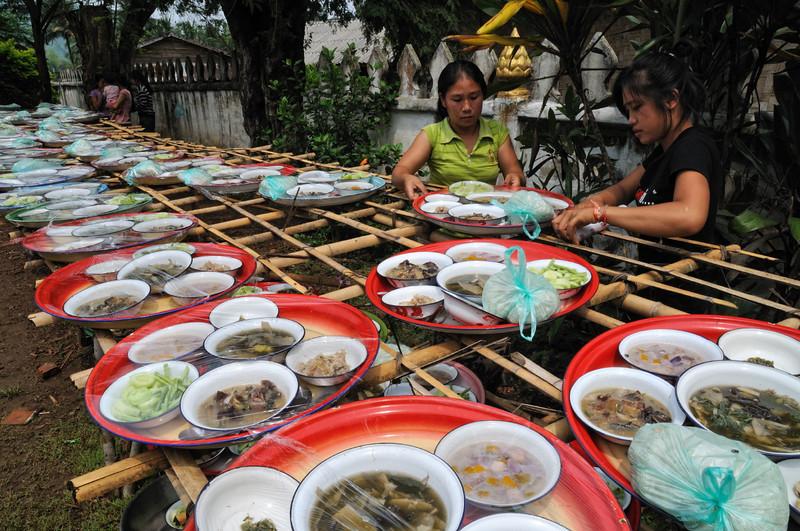 Das Essen für die aus Luang Prabang eingeladenen Mönche wird vorbereitet; Feierlichkeiten zur Einweihung einer Stupa am Tempel im kleinen Ort Ban Naxao in der Nähe von Luang Prabang