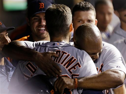 . Detroit Tigers\' Torii Hunter , right, hugs J.D. Martinez after Martinez hit a three-run home run off Cleveland Indians relief pitcher Cody Allen in the ninth inning of a baseball game, Tuesday, Sept. 2, 2014, in Cleveland. Hunter and Steven Moya scored on the play. The Tigers defeated the Indians 4-2. (AP Photo/Tony Dejak)