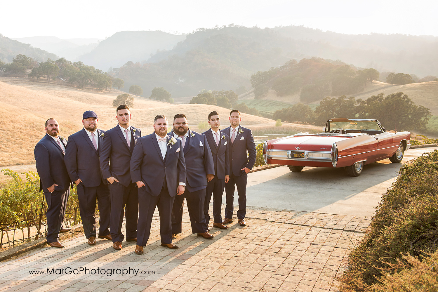 groom and groomsmen with red car at Taber Ranch Vineyards