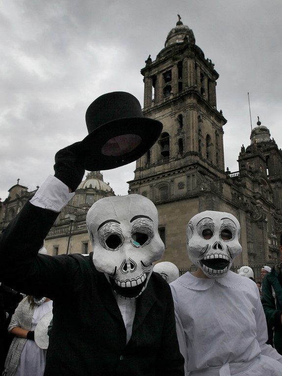 . A couple wearing skull masks perform as part of the Day of the Dead festivities in Mexico City, Thursday, Oct. 27, 2016. The holiday honors the dead as friends and families gather in cemeteries to decorate their loved ones\' graves and hold vigil through the night on Nov. 1 and 2. (AP Photo/Marco Ugarte)