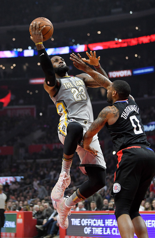 . Cleveland Cavaliers forward LeBron James, left, shoots as Los Angeles Clippers guard Sindarius Thornwell defends during the first half of an NBA basketball game Friday, March 9, 2018, in Los Angeles. (AP Photo/Mark J. Terrill)