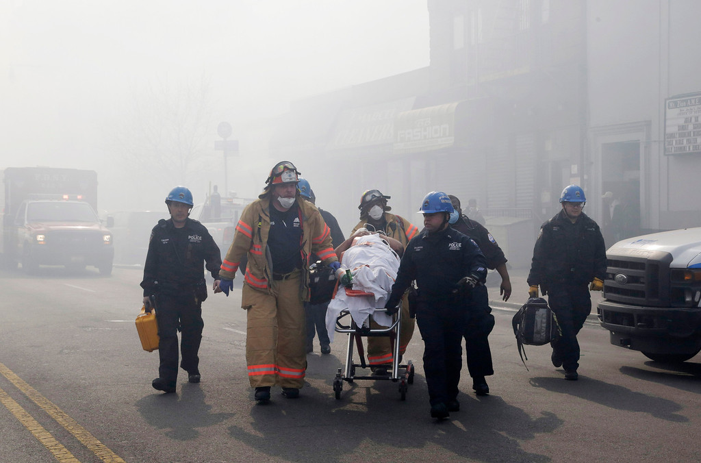 . Rescue workers remove an injured person on a stretcher following a building explosion and collapse in East Harlem, Wednesday, March 12, 2014 in New York. (AP Photo/Mark Lennihan)
