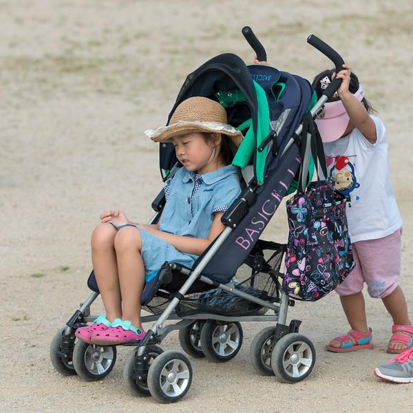Girl pushing her sister in a baby stroller, Seoul, South Korea