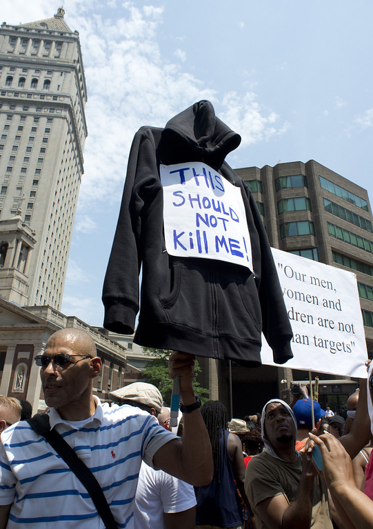 """. A man holds up a black hoodie in memory of Trayvon Martin at a rally July 20, 2013 in New York. Hundreds were in attendence at the NYC rally \""""Justice for Trayvon.\"""" Civil rights groups mobilized for protests in cities across the United States on Saturday amid charged emotions over the not-guilty verdict in the shooting death of unarmed black teenager Trayvon Martin. The demonstrations, which began in Miami, come a day after US President Barack Obama publicly identified with the slain 17-year-old and the deep frustrations felt among African-Americans over the verdict.  DON EMMERT/AFP/Getty Images"""