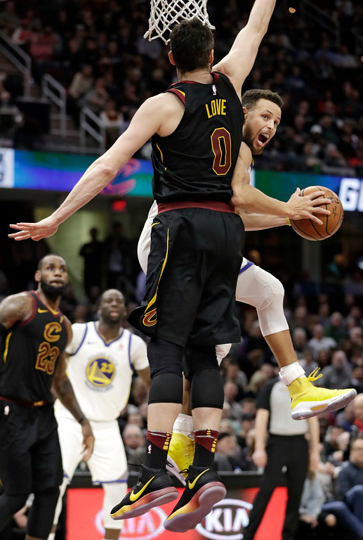 . Golden State Warriors\' Stephen Curry, front right, drives to the basket against Cleveland Cavaliers\' Kevin Love, front left, in the second half of an NBA basketball game, Monday, Jan. 15, 2018, in Cleveland. (AP Photo/Tony Dejak)