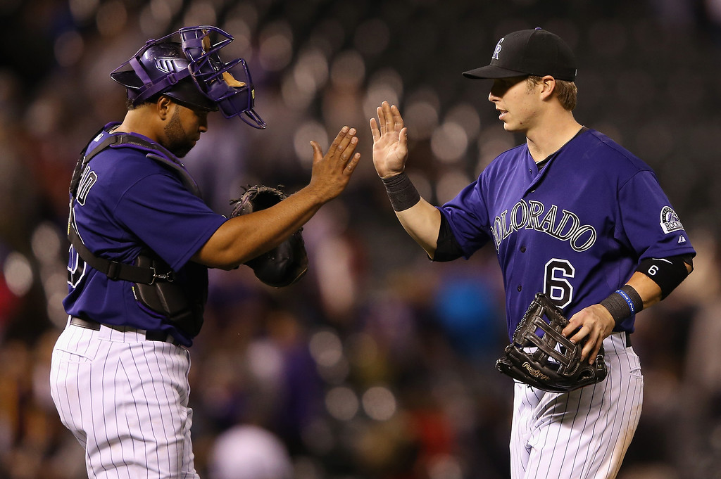 . Wilin Rosario #20 and Corey Dickerson #6 of the Colorado Rockies celebrate their 8-2 victory over the San Francisco Giants at Coors Field on April 21, 2014 in Denver, Colorado.  (Photo by Doug Pensinger/Getty Images)