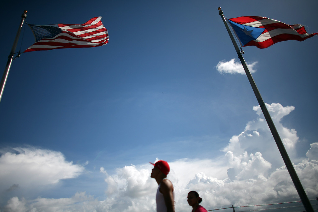 . In this Oct. 2, 2012 photo, U.S. And Puerto Rico\'s flags fly as tourists walk along the dock where a cruise ship anchors in Old San Juan, Puerto Rico.   (AP Photo/Ricardo Arduengo)