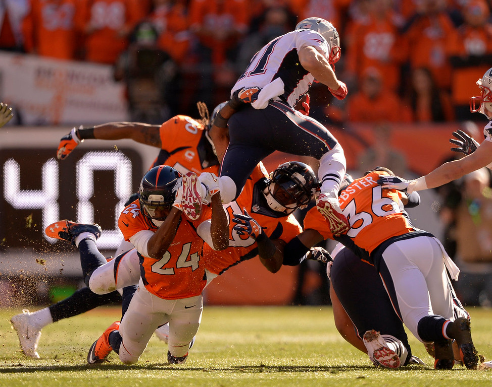 . New England Patriots wide receiver Julian Edelman (11) tries to leap over the Broncos but Denver Broncos cornerback Champ Bailey (24) has him by the foot during the first quarter. The Denver Broncos vs. The New England Patriots in an AFC Championship game  at Sports Authority Field at Mile High in Denver on January 19, 2014. (Photo by John Leyba/The Denver Post)