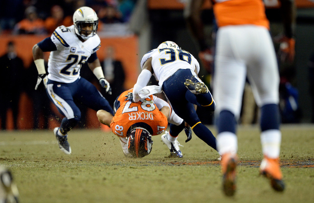 . Denver Broncos wide receiver Eric Decker (87) gets taken down by San Diego Chargers strong safety Marcus Gilchrist (38) during the second half.  The Denver Broncos vs. the San Diego Chargers at Sports Authority Field at Mile High in Denver on December 12, 2013. (Photo by Hyoung Chang/The Denver Post)