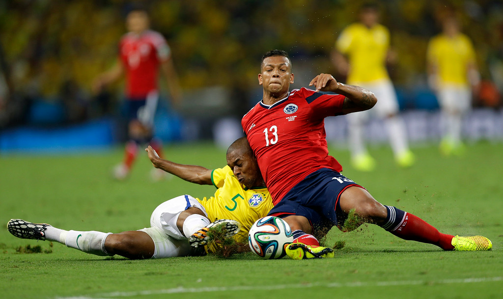 . Brazil\'s Fernandinho collides into Colombia\'s Fredy Guarin while being defended during the World Cup quarterfinal soccer match between Brazil and Colombia at the Arena Castelao in Fortaleza, Brazil, Friday, July 4, 2014. (AP Photo/Andre Penner)