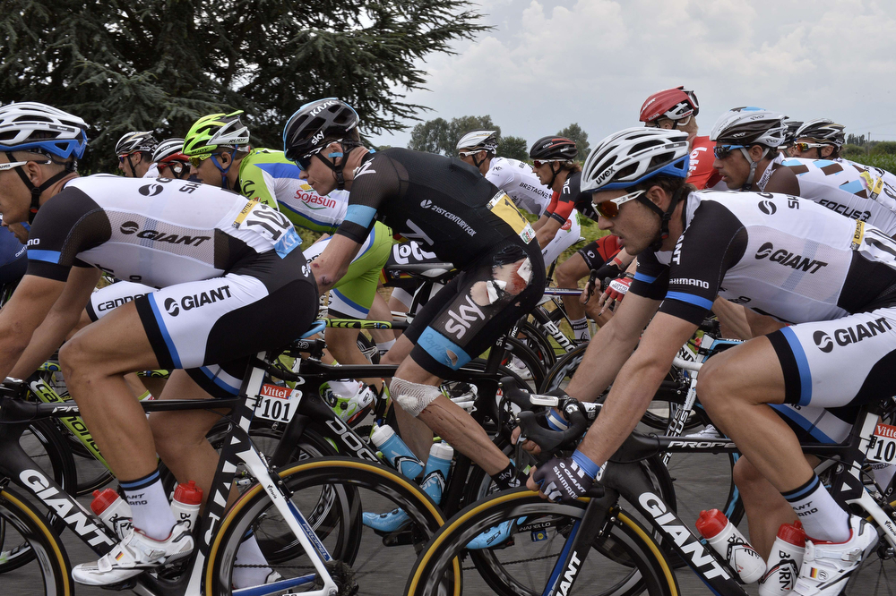 Description of . Britain's Christopher Froome injured rides in the pack after a fall during the 163.5 km fourth stage of the 101st edition of the Tour de France cycling race on July 8, 2014 between Le Touquet-Paris-Plage and Lille, northern France.  (JEFF PACHOUD/AFP/Getty Images)