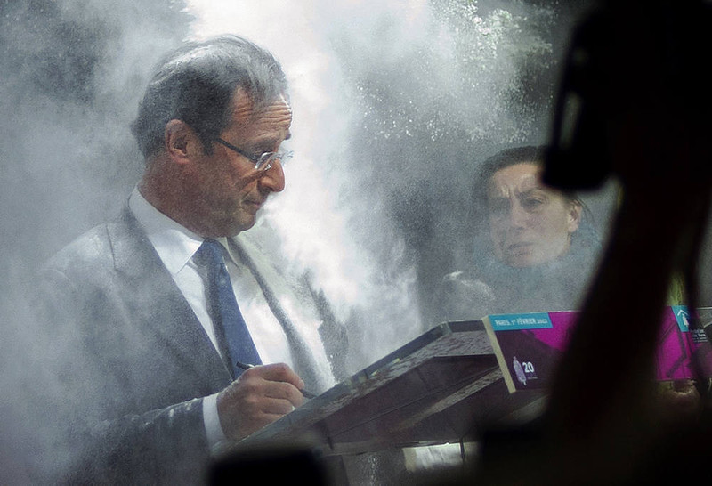 . France\'s opposition Socialist Party (PS) candidate for the 2012 French presidential election Francois Hollande (C) receives flour, thrown by a woman (R) while he was signing a pact on French housing crisis with representatives of the Abbé Pierre Foundation on February 1, 2012 in Paris. AFP PHOTO / FRED DUFOUR/AFP/Getty Images