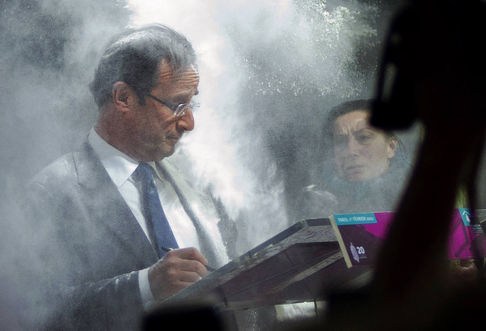 Description of . France's opposition Socialist Party (PS) candidate for the 2012 French presidential election Francois Hollande (C) receives flour, thrown by a woman (R) while he was signing a pact on French housing crisis with representatives of the Abbé Pierre Foundation on February 1, 2012 in Paris. AFP PHOTO / FRED DUFOUR/AFP/Getty Images