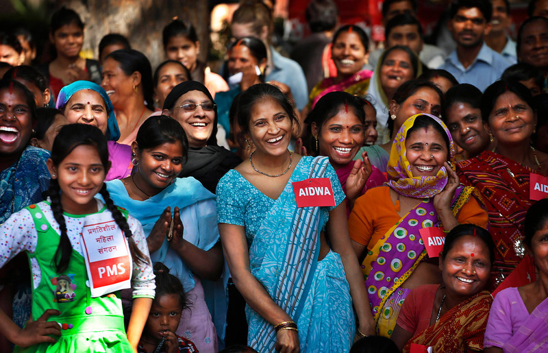 . Indian women laugh as they watch police coming down hard on an eve teaser as they watch a play sensitizing women to sexual abuse and ways to raise their voice against it on occasion of International Women\'s Day, in New Delhi, India, Friday, March 8, 2013. (AP Photo/Saurabh Das)