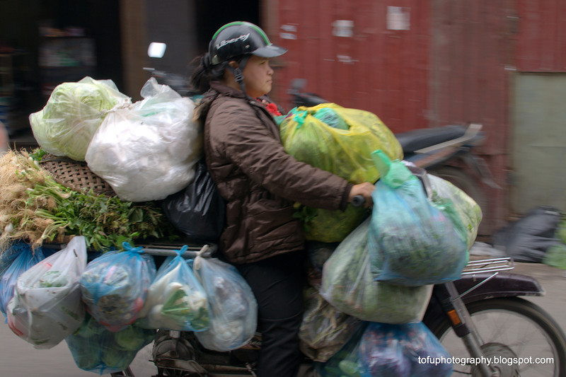 Woman with an overloaded motorbike in Hanoi, Vietnam in January 2012
