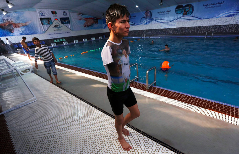 Description of . Abbas Karimi, 14, who was born without arms, walks at a public swimming pool in Kabul, February 18, 2013. Karimi has ambitions to earn a gold medal for his country in the world Paralympic games. If he gets the support he needs, the teenager will be the first Afghan to represent his county as a swimmer in the games next due to take place in Brazil in 2014. REUTERS/Omar Sobhani