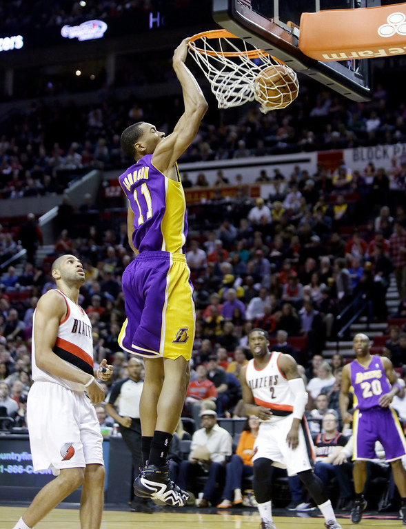 . Los Angeles Lakers forward Wesley Johnson, right, scores on a fast break against Portland Trail Blazers forward Nicolas Batum, of France, during the first half of an NBA basketball game in Portland, Ore., Monday, March 3, 2014. (AP Photo/Don Ryan)