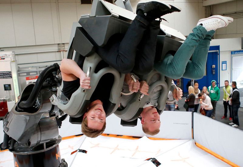 . Visitors enjoy a ride on an industrial robot at the Hanover Messe on the first day of the industrial trade fair, in Hanover April 8, 2013. The Hanover fair runs from April 8 -12. REUTERS/Fabrizio Bensch