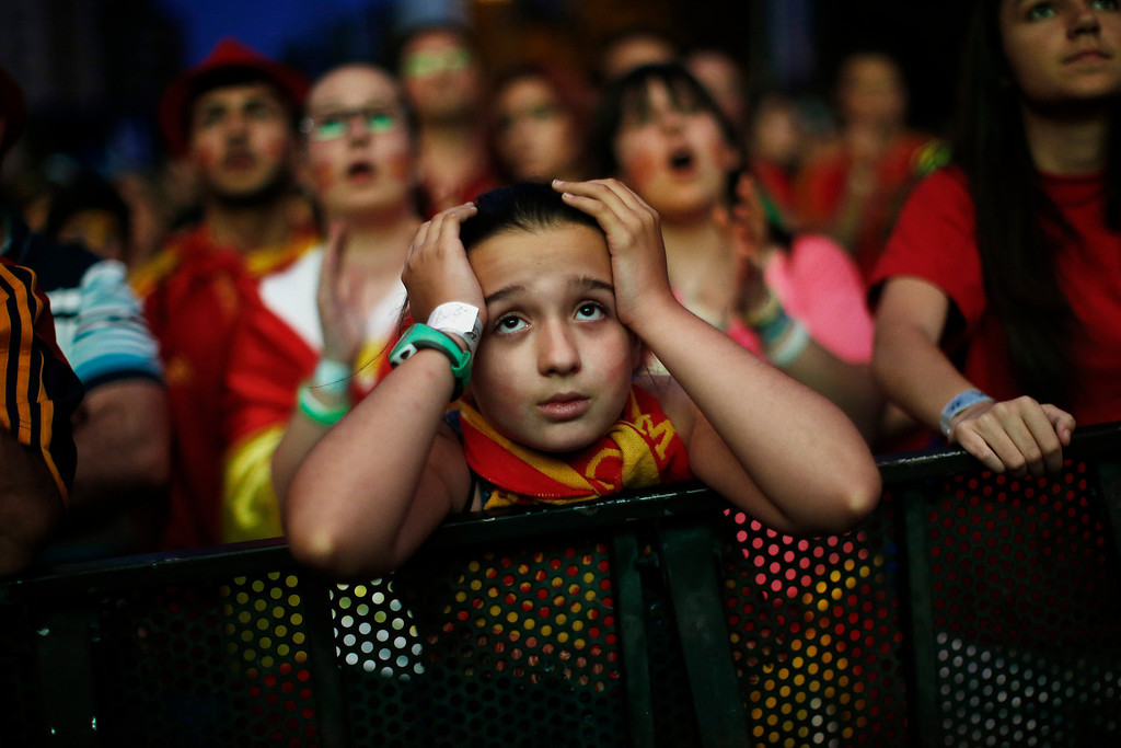 . A Spanish soccer fan holds her head as she watches, on a giant display, the World Cup soccer match between Spain and Chile, in Madrid, Spain, Wednesday, June 18, 2014. (AP Photo/Andres Kudacki)