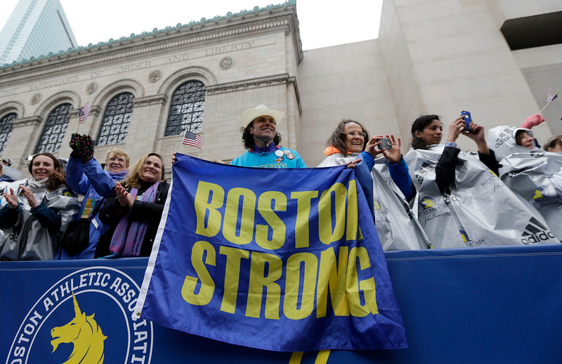 ". Carlos Arredondo, a 2013 Boston Marathon first-responder, holds a ""Boston Strong\"" banner beside his wife Melida, right, in the grandstand near the Boston Marathon finish line Monday, April 20, 2015 in Boston. (AP Photo/Elise Amendola)"