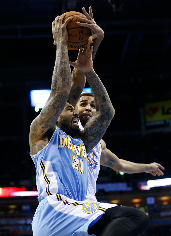 . Oklahoma City Thunder guard Thabo Sefolosha (25) gets his hand on the ball as Denver Nuggets forward Wilson Chandler (21) goes up for a shot in the first quarter of an NBA basketball game in Oklahoma City, Monday, Nov. 18, 2013. (AP Photo/Sue Ogrocki)