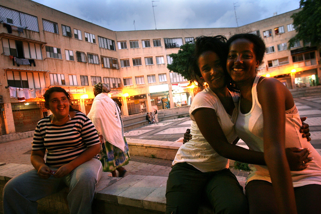 . NETANYA, ISRAEL - JULY 2: Ethiopian Jewish teenage girls, both born in Israel, with their Israeli friend (L) in the local shopping plaza in the neighborhood where their families settled a few years ago, on July 2, 2007 in Netanya, central Israel. Some 2,500 Ethiopians of Jewish origin remain in the East African country as Israel slowly brings them over, a few dozen at a time, on commercial flights. Since 1984, more than 73,000 Ethiopian Jews have been settled in Israel. (Photo by Uriel Sinai/Getty Images)