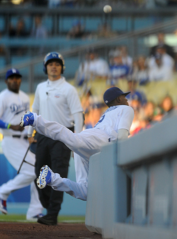 . Dodgers second baseman Dee Gordon collides with the wall while trying to catch a foul ball in the first inning against the Padres, Friday, July 11, 2014, at Dodger Stadium. (Photo by Michael Owen Baker/Los Angeles Daily News)