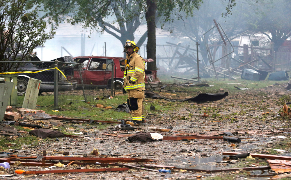 Description of . A firefighter pauses while surveying the blast zone destroyed by an explosion at a fertilizer plant during search and rescue efforts in West, Texas, Thursday, April 18, 2013.  A massive explosion at the West Fertilizer Co. killed as many as 15 people and injured more than 160, officials said overnight.  (AP Photo/LM Otero)