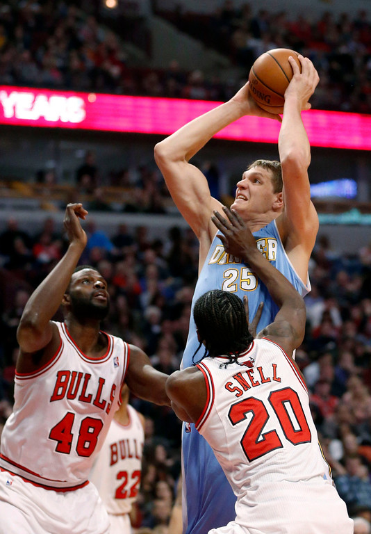 . Denver Nuggets center Timofey Mozgov, right, drives between Chicago Bulls center Nazr Mohammed (48) and Tony Snell (20) during the first half of an NBA basketball game Friday, Feb. 21, 2014, in Chicago. (AP Photo/Charles Rex Arbogast)