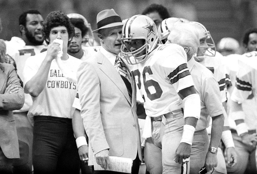 . Head coach Tom Landry of the Dallas Cowboys sends in a play from the sideline with running back Preston Pearson in Super Bowl XII. (AP Photo/Harry Cabluck)