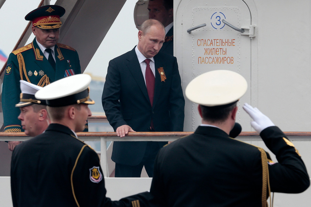 . Russian President Vladimir Putin, followed by Defense Minister Sergei Shoigu, left, arrives on a boat after inspecting battleships during a navy parade marking the Victory Day in Sevastopol, Crimea, Friday, May 9, 2014. (AP Photo/Ivan Sekretarev)